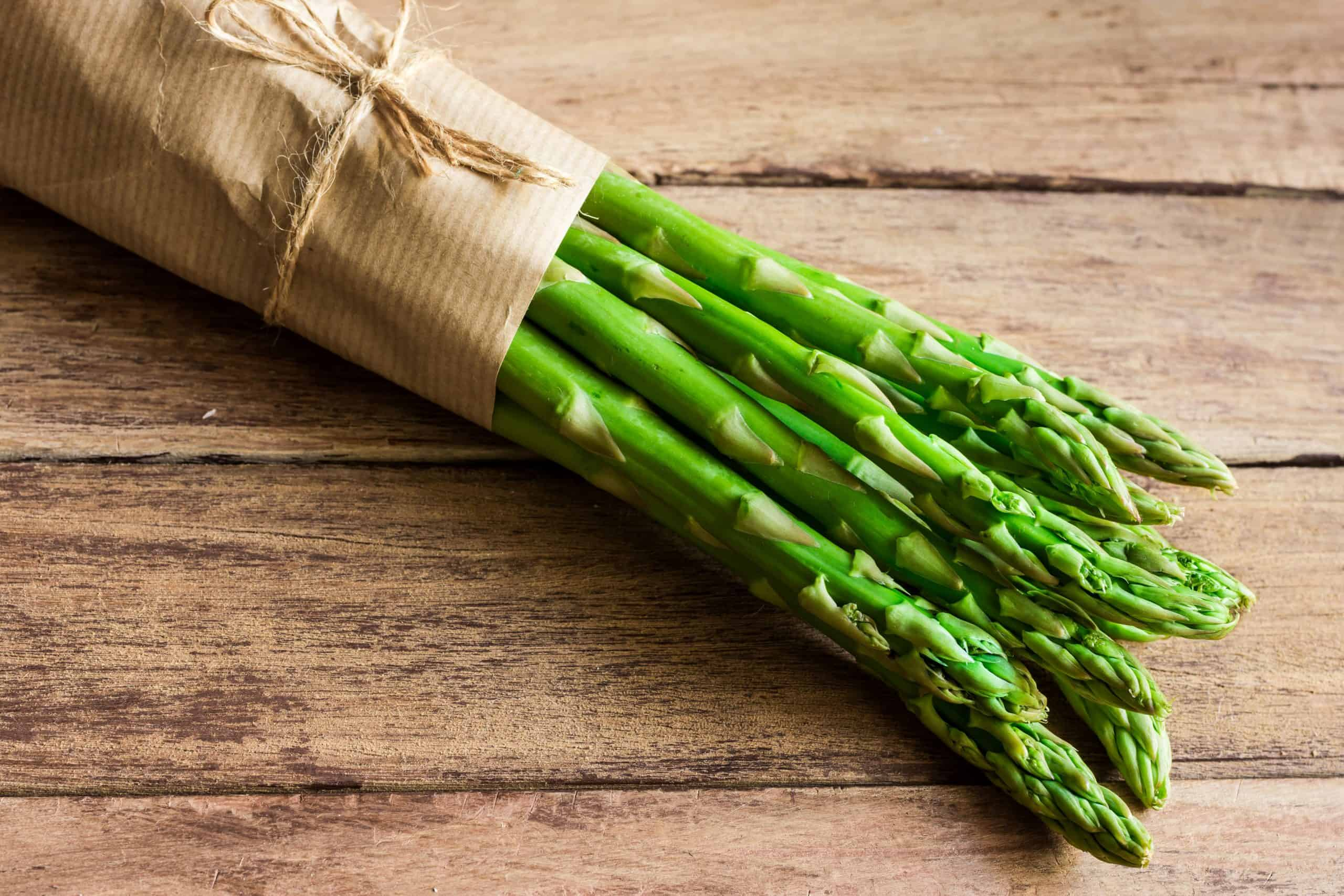 Bunch of green fresh asparagus tied with twine lying on aged plank wood table, menu template, top view, copy space for text